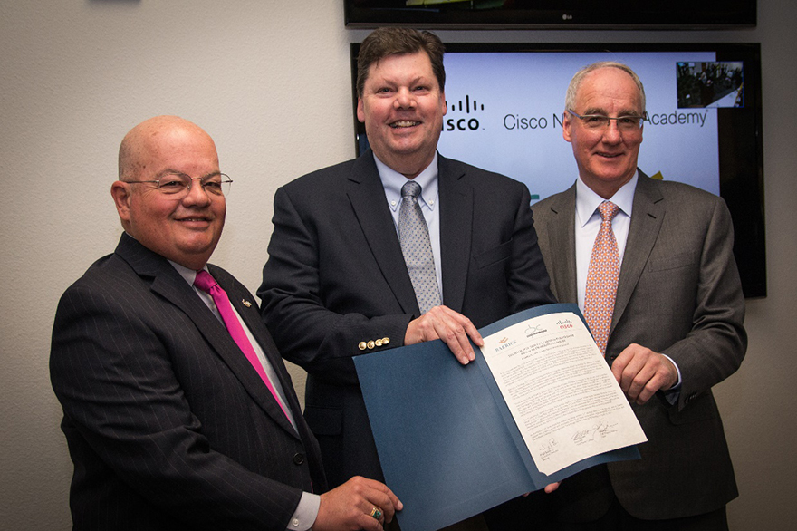 Great Basin College president Dr. Mark Curtis, from left, Cisco corporate social responsibility manager John Bjerke and Barrick USA executive director Nigel Bain pose with the signed collaborative learning agreement of the Networking Academy at the High Tech Career Center at Great Basin College in Elko on Thursday, April 20, 2017.